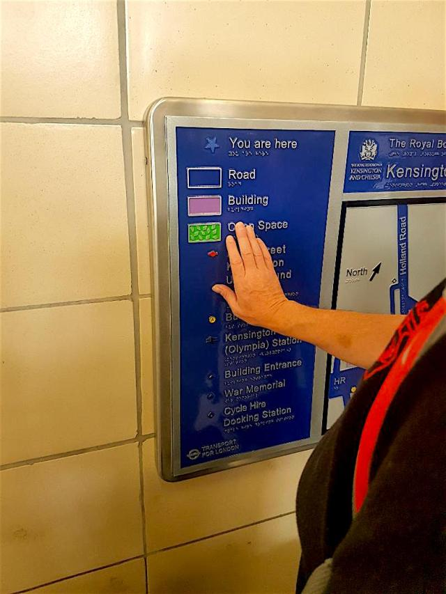 The image depicts a visually impaired person touching the tactile map with his right hand. He is feeling the raised letters that read Open Space.